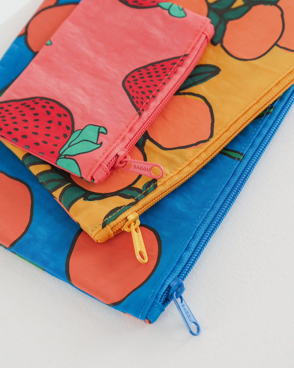 close up of 3 nylon pouches in assorted sizes in 3 different patterns: blue with red cherries, marigold with orange tree print, pink with red strawberries