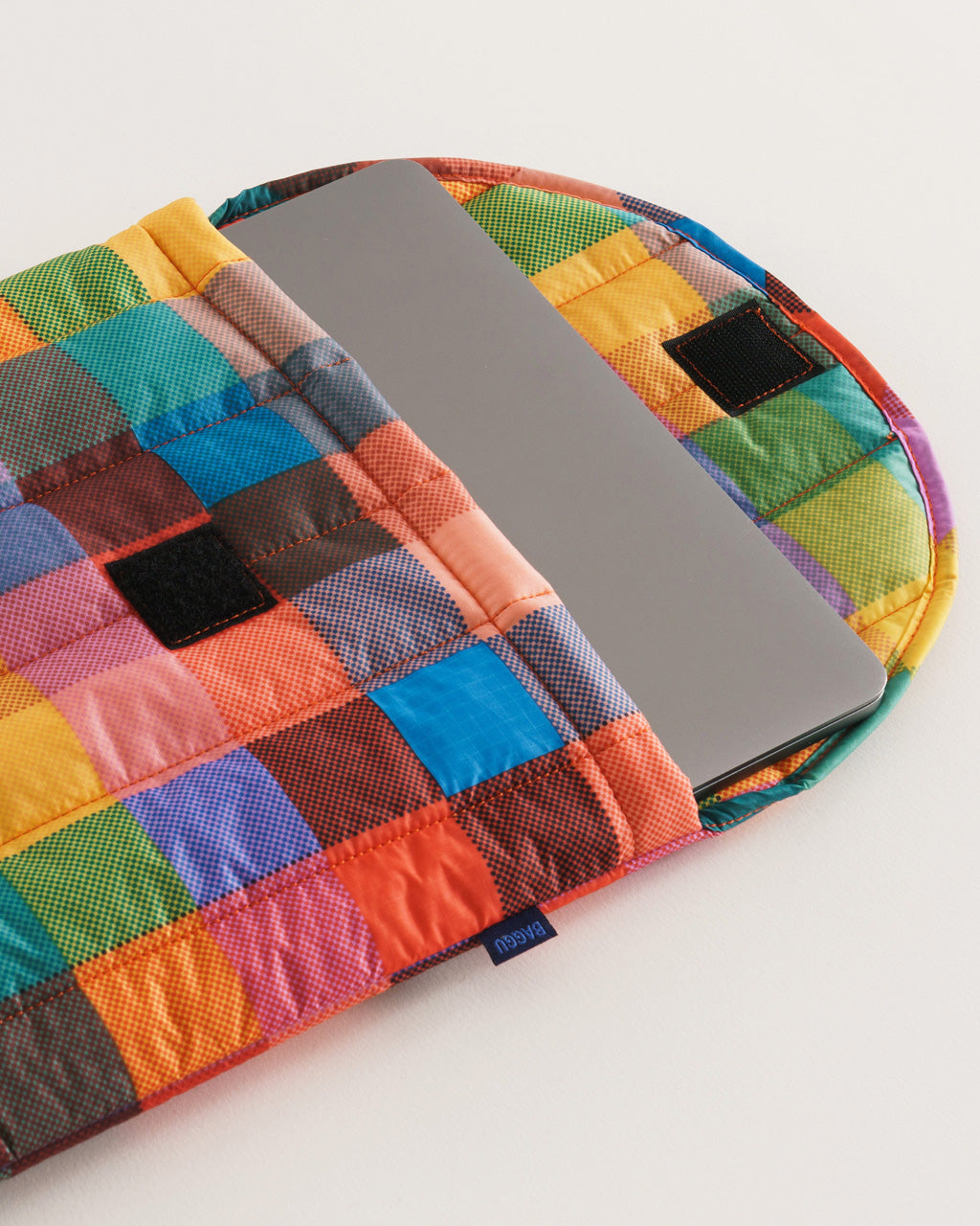 "16"" laptop sleeve in multicolored madras plaid pattern shown with laptop"