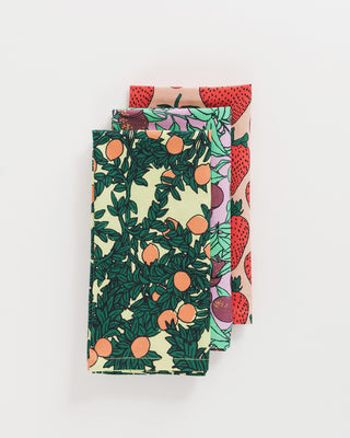 set of 3 reusable cloth napkins shown folded and stacked in orange, plum, and strawberry patterns