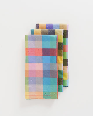set of 3 reusable cloth napkins shown folded and stacked in multicolored madras plaid print