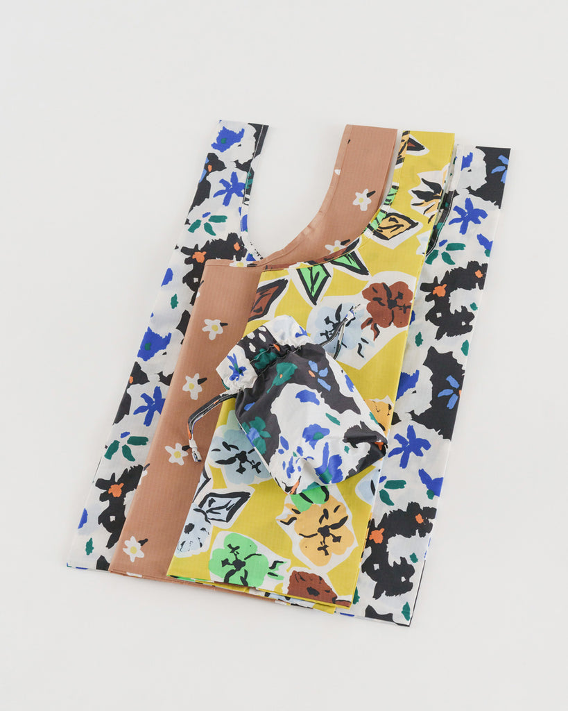 set of 3 standard baggu bags in various floral prints shown in a flat stack with matching carrying pouch