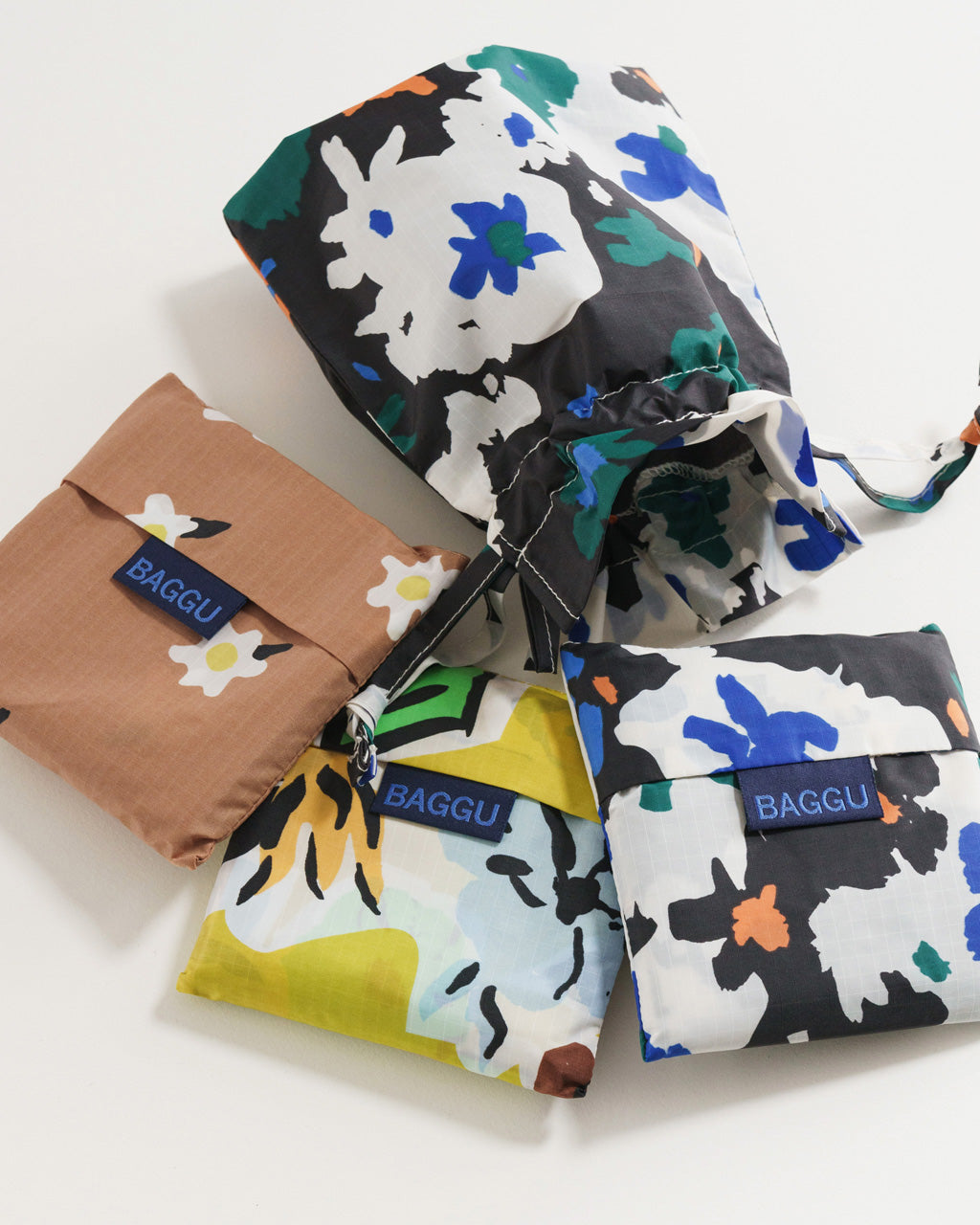 set of 3 standard baggu bags in various floral prints shown folded with matching carrying pouch