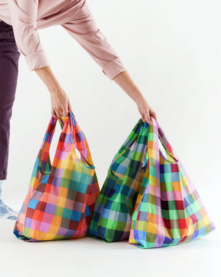 model holding set of 3 standard baggu bags in multicolored madras plaid patterns