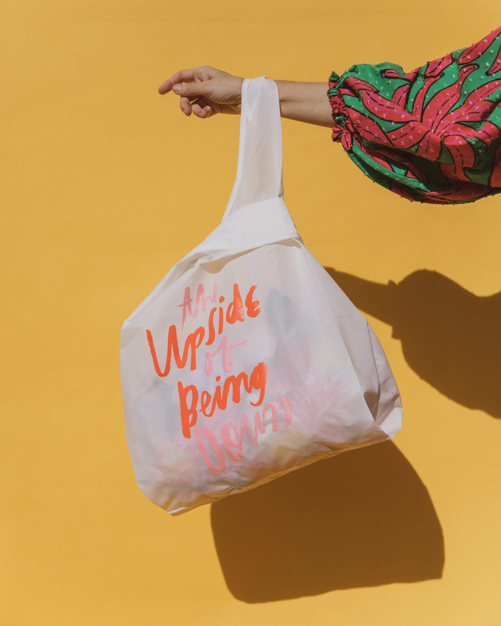 a white baggu with the words the upside of being down shown in front of a yellow background being