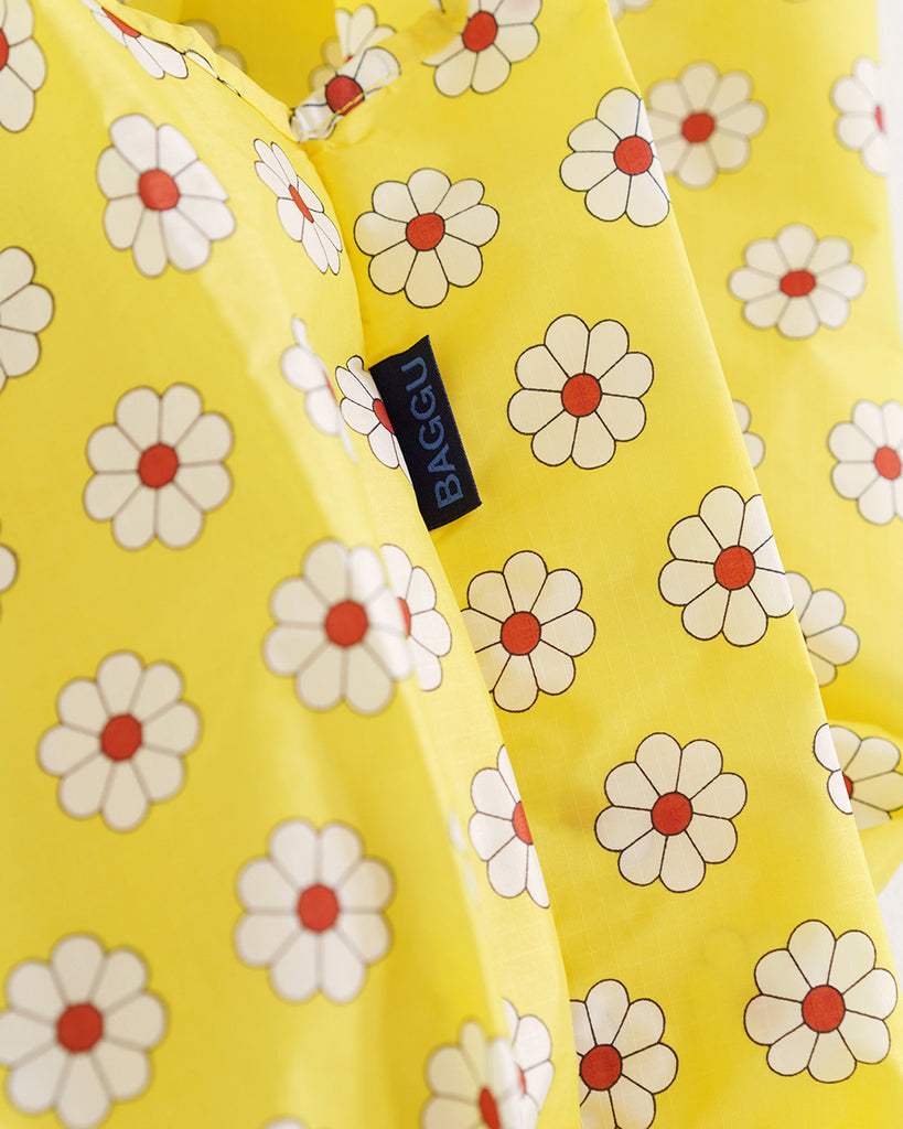 close up of black BAGGU tag on a yellow bag with red and white flowers