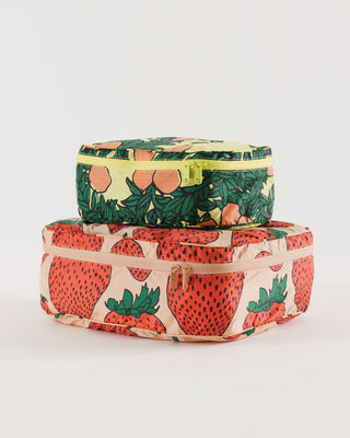 set of two storage cubes stacked. 1 blush zippered cube with large red strawberry print, 1 yellow zippered cube with all over orange tree print