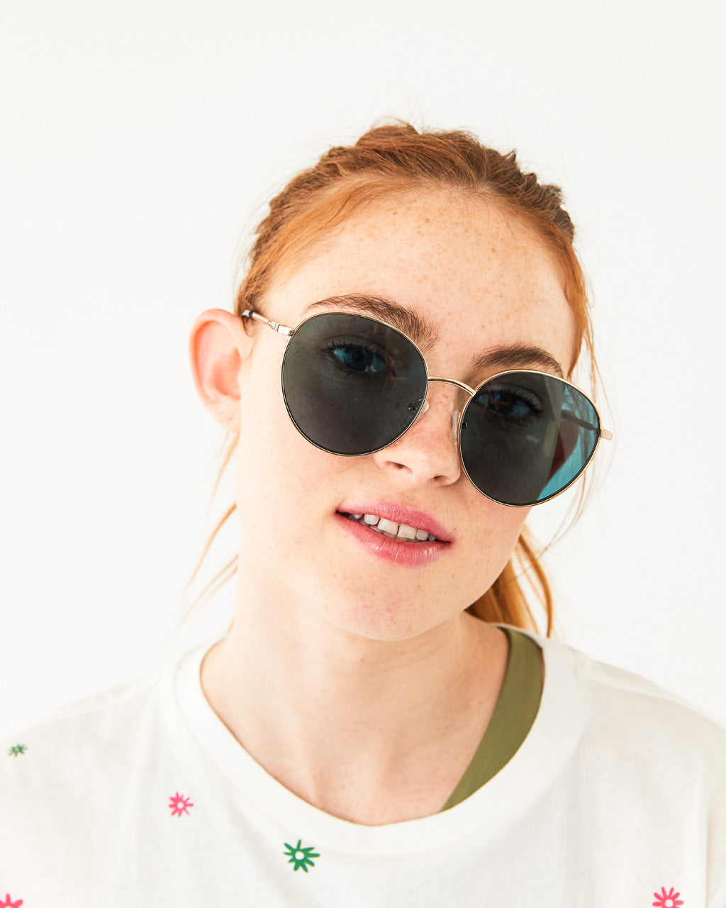 Oversized round sunglasses with dark green lens shown on model