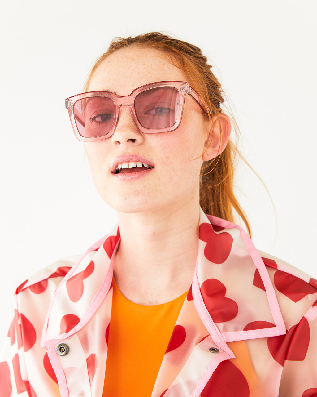 woman in an orange shirt and rain jacket wearing pink square sunglasses