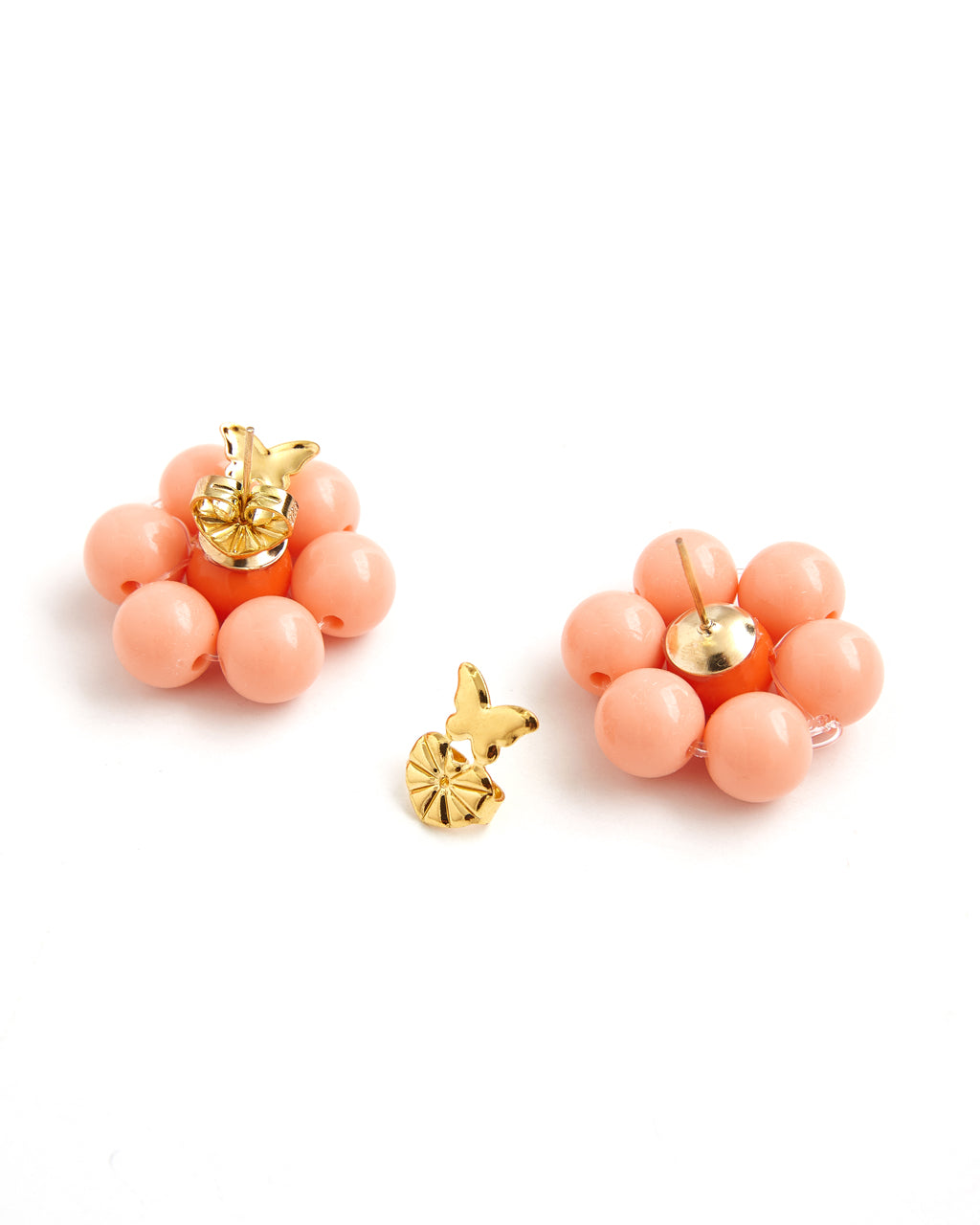 back view of peach beaded earrings with orange center