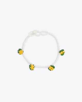 white beaded bracelet with yellow and green bead accents