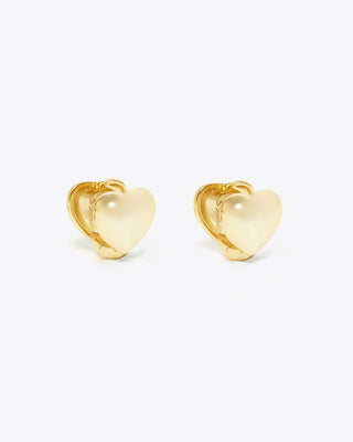 dainty gold huggie earrings on a beige background