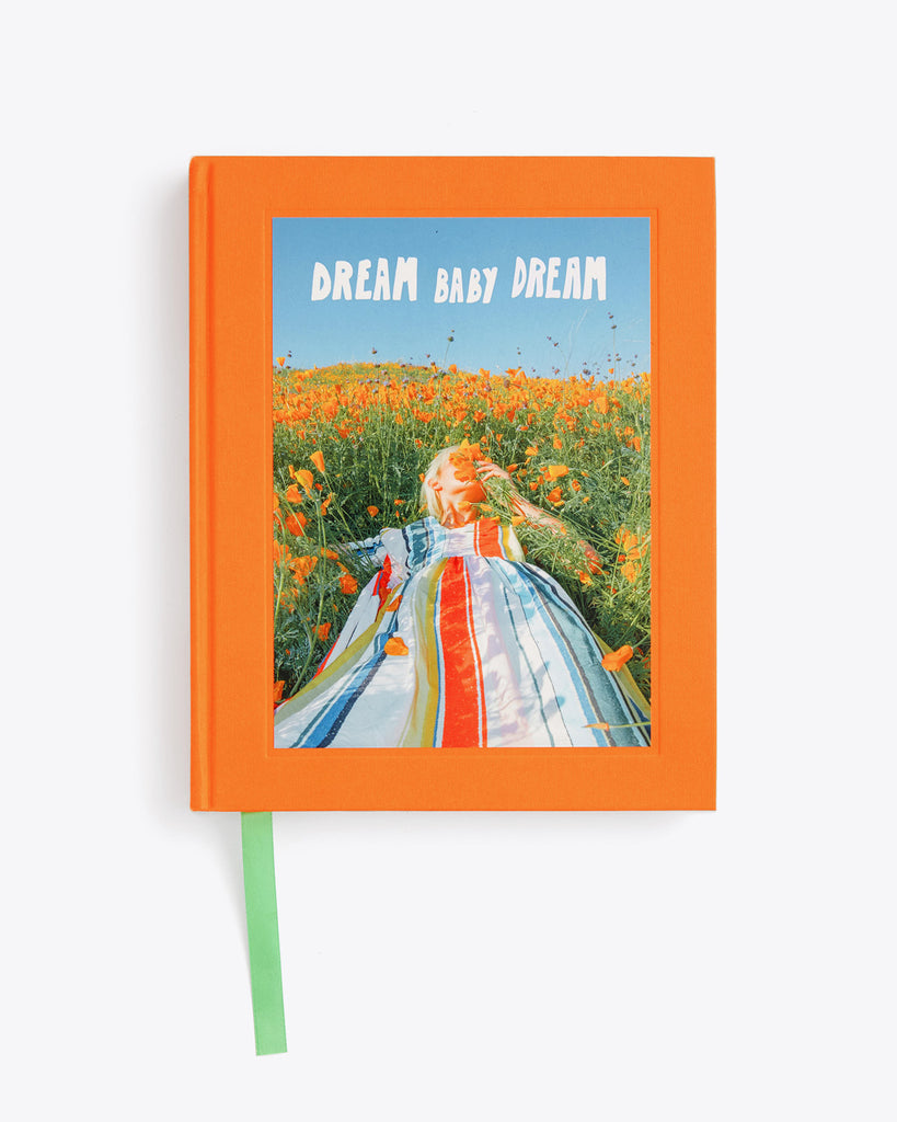orange hard cover book with outdoor shot featuring a lady laying in the grass smelling the flowers