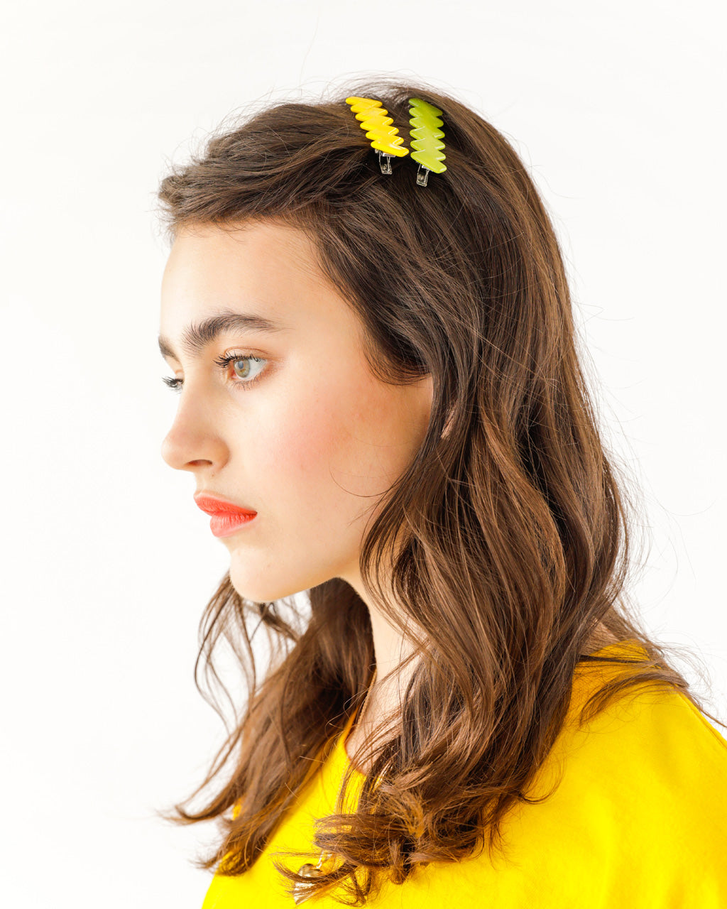 brunette model shown wearing one yellow and one green hair clip