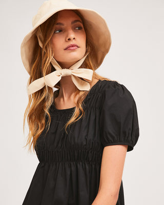 model wearing beige bucket hat with tie strap around neck with black blouse