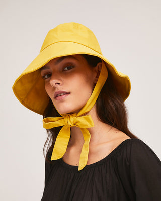 model wearing yellow bucket hat with tie strap around neck with black blouse