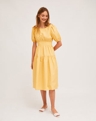 model wearing yellow midi dress with white slide sandals