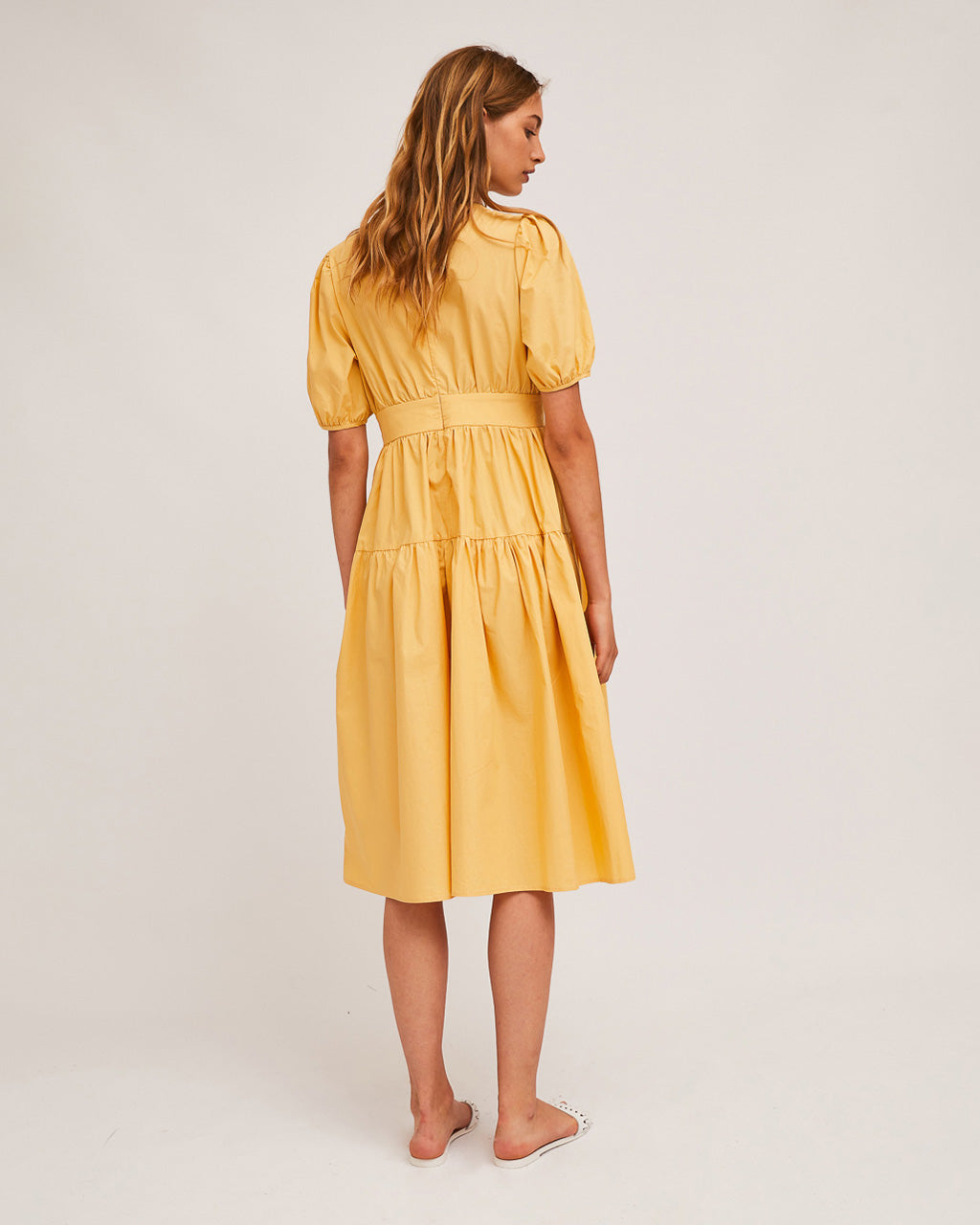 back view of model wearing yellow midi dress with white slide sandals