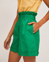 model wearing yellow sleeveless blouse and green high waist paper bag shorts