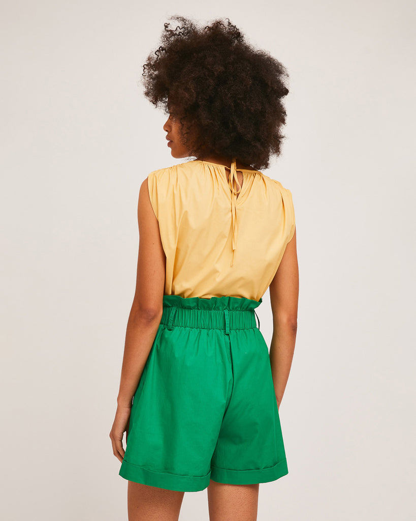 back view of model wearing yellow sleeveless blouse and green high waist paper bag shorts