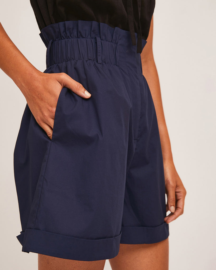close up shot of model wearing black sleeveless blouse and navy blue high waist paper bag shorts