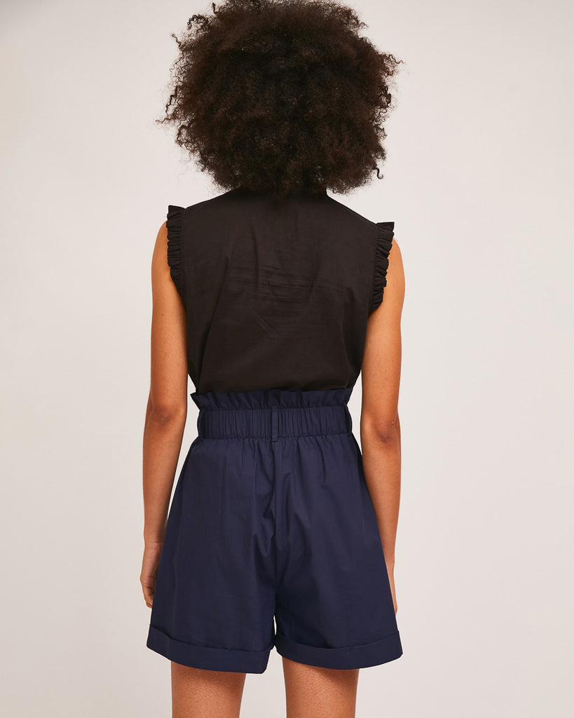 back view of model wearing black sleeveless blouse and navy blue high waist paper bag shorts