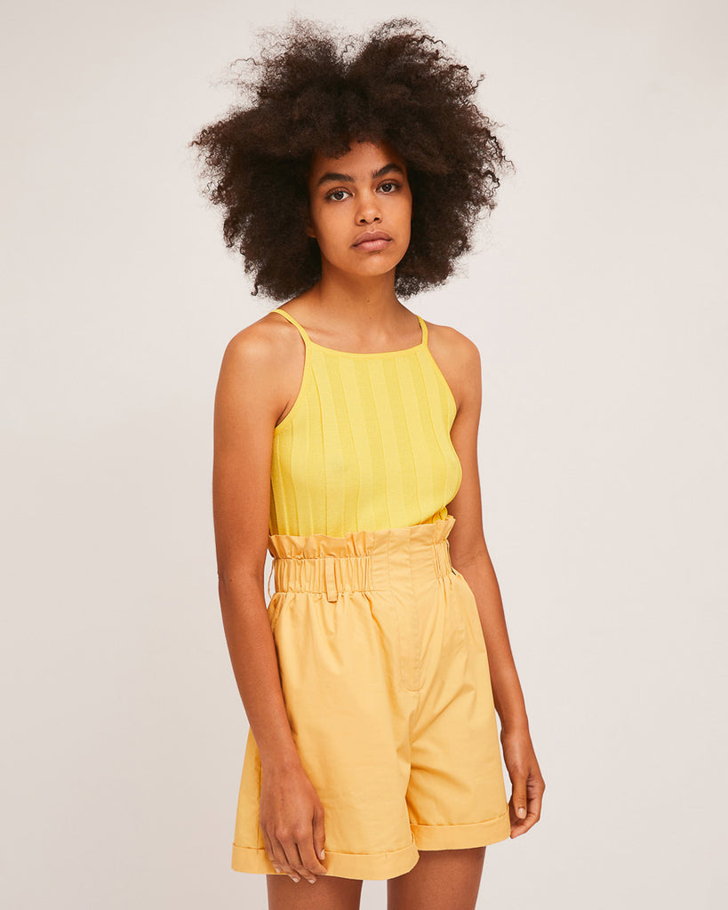 model wearing yellow tank top with yellow high waist paper bag shorts
