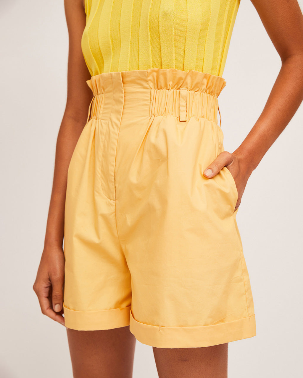 detail shot of model wearing yellow tank top with yellow high waist paper bag shorts