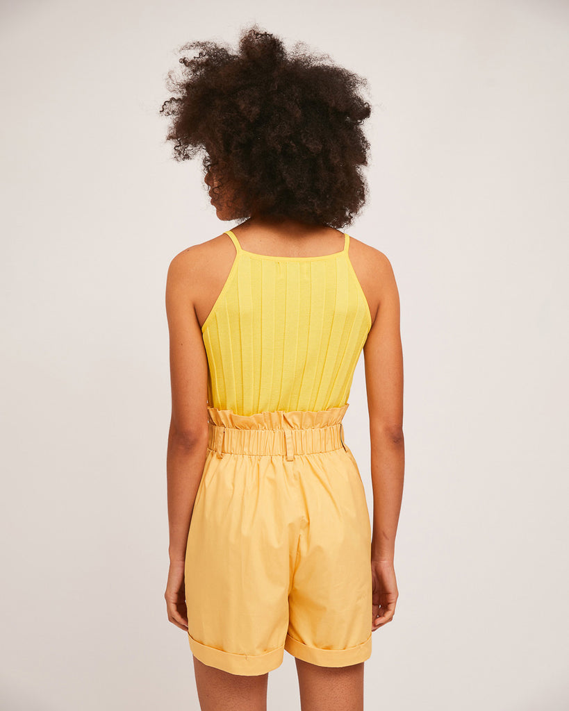 back view of model wearing yellow tank top with yellow high waist paper bag shorts