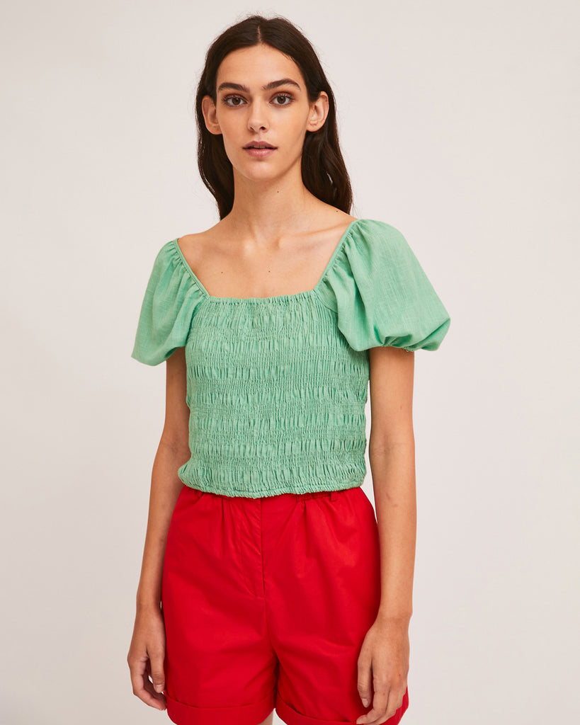 model wearing green shirred blouse with puff sleeves and red shorts