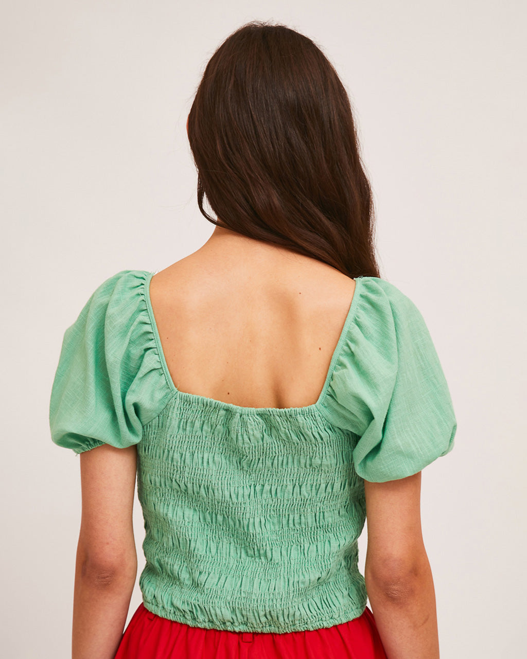 back view of model wearing green shirred blouse with puff sleeves and red shorts