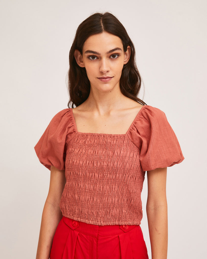 model wearing pink shirred blouse with puff sleeves and red shorts