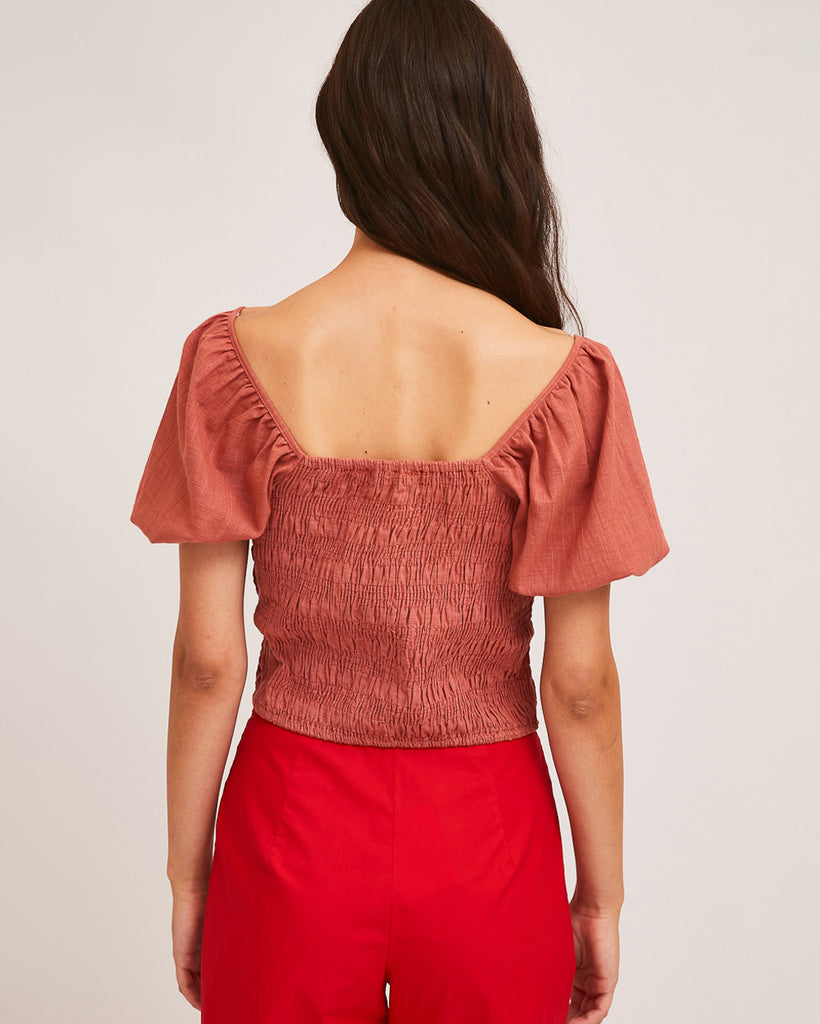 back view of model wearing pink shirred blouse with puff sleeves and red shorts