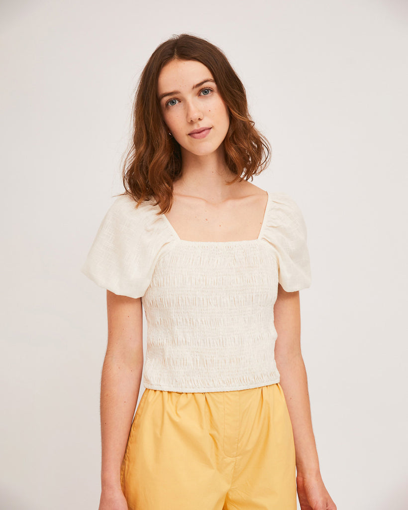 model wearing white shirred blouse with puff sleeves and yellow shorts