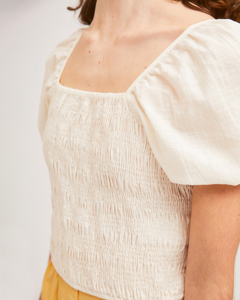 close up shot of model wearing white shirred blouse with puff sleeves and yellow shorts