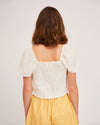 back of model wearing white shirred blouse with puff sleeves and yellow shorts