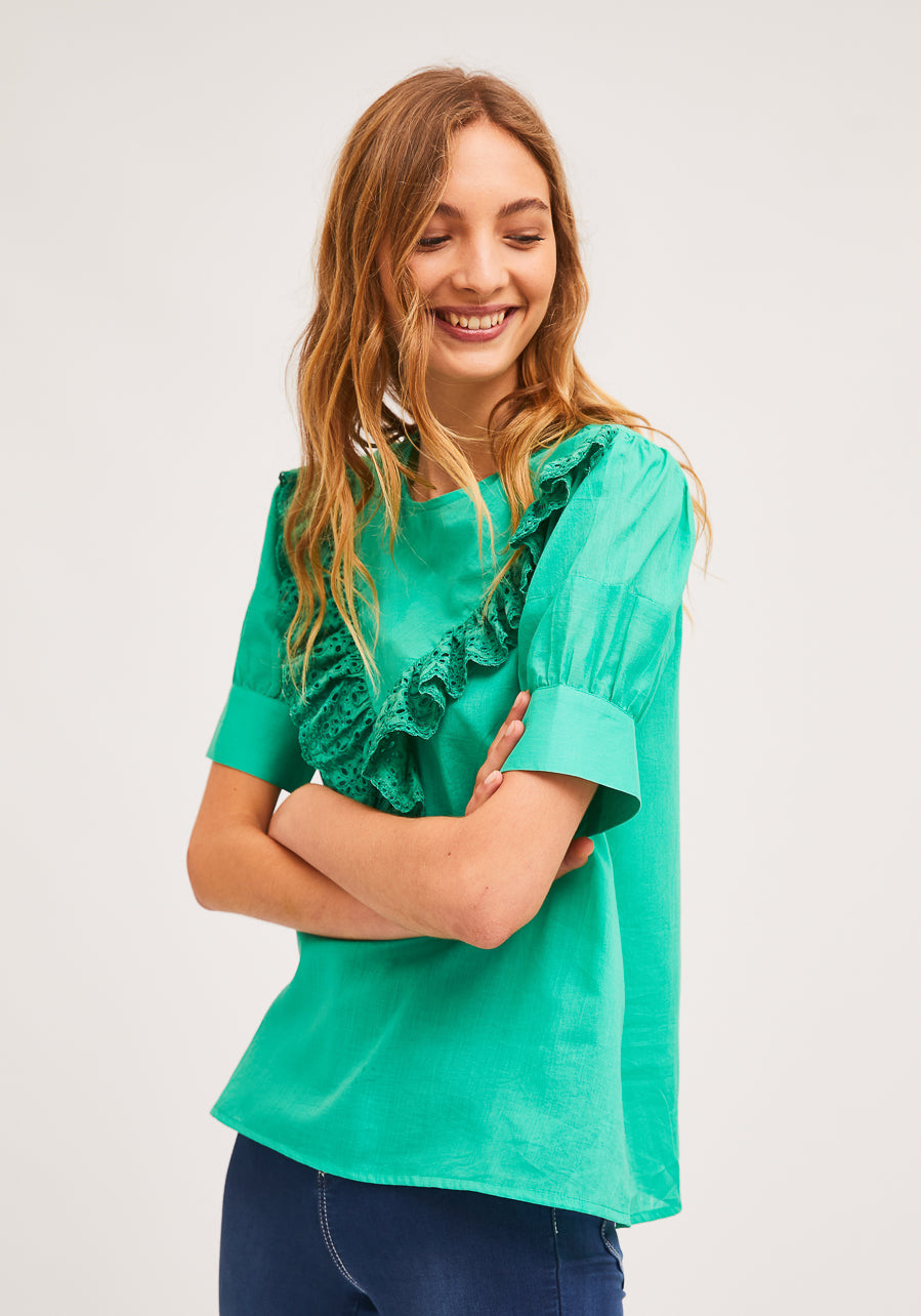 model wearing green ruffle-front blouse with eyelet detail and blue jeans