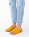 mustard yellow faux leather mules with a small heel shown on model wearing light colored ankle jeans