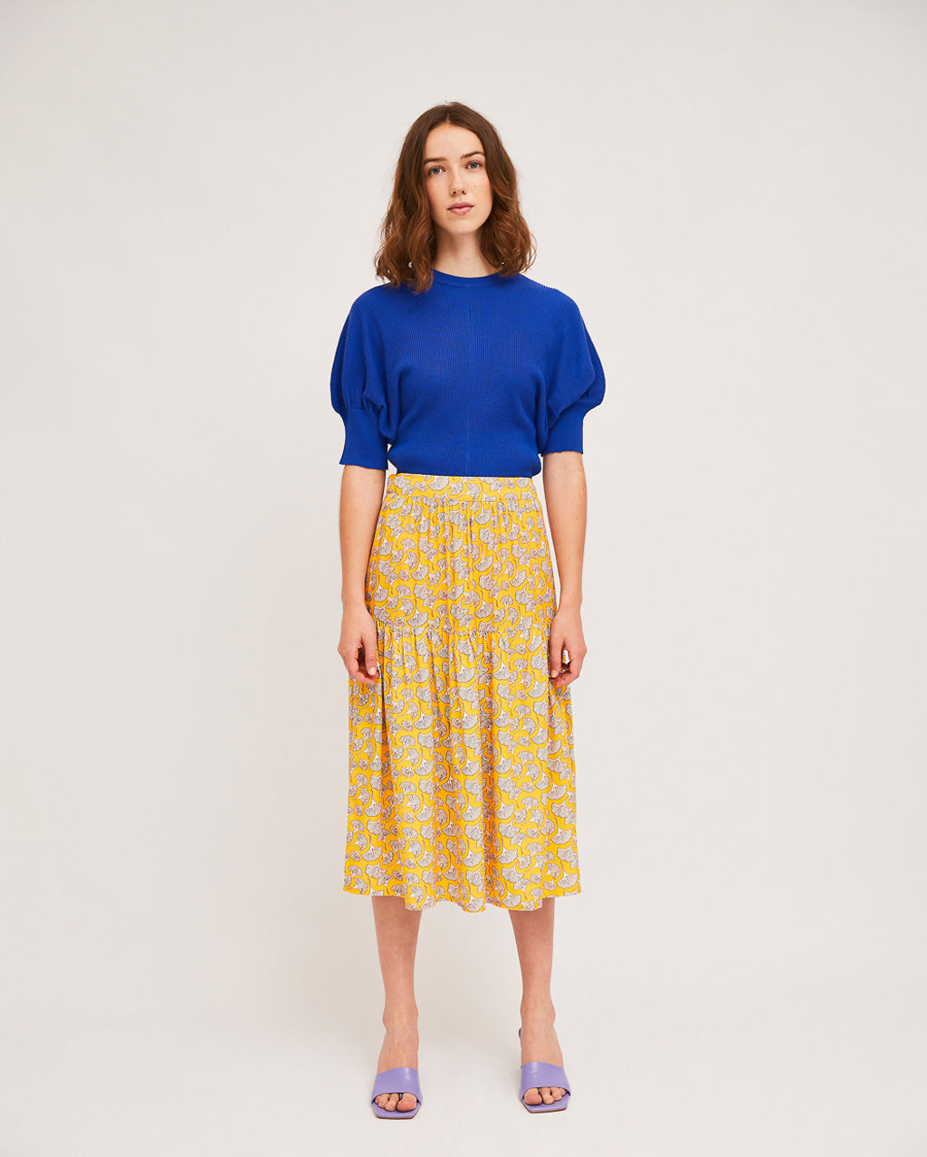 model wearing blue puff sleeve sweater with yellow print skirt and purple slide heels