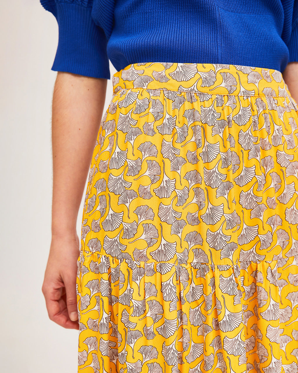 model wearing blue puff sleeve sweater with yellow print skirt