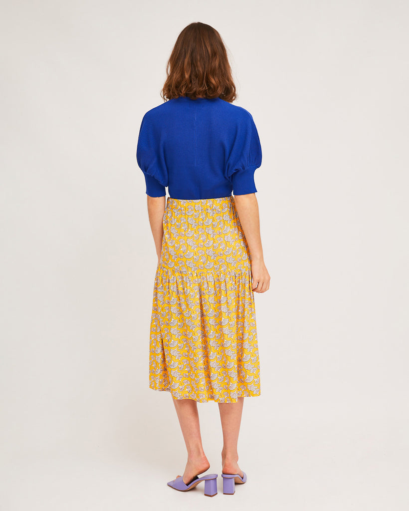 back view of model wearing blue puff sleeve sweater with yellow print skirt and purple slide heels