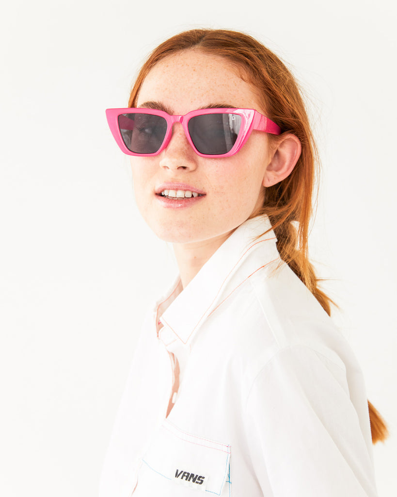 pink neon cat eye sunglasses with a black lens shown on model