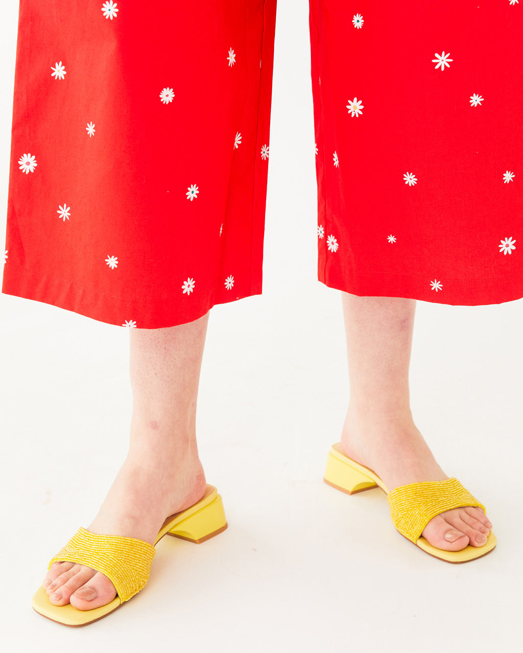 yellow slip on sandal featuring a beaded upper strap and a low heel shown on model wearing a red jumpsuit with a white daisy pattern