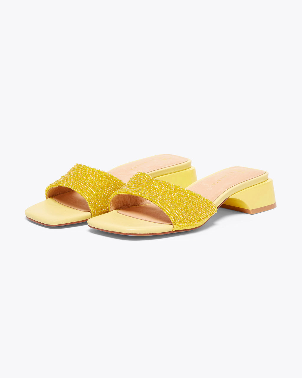 yellow slip on sandal featuring a beaded upper strap and a low heel