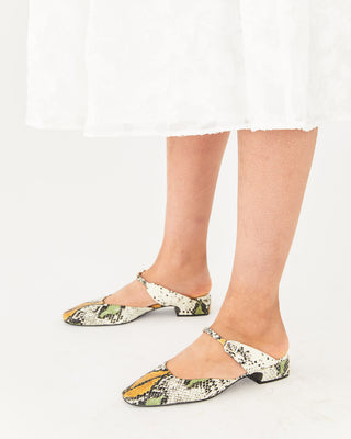snake skin mules with a low heel and an adjustable strap shown on model wearing a white below the knee skirt