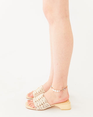 beige slip on sandal with a low heel and a seashell textile feature on upper strap shown on model wearing a rainbow pearl ankle bracelet
