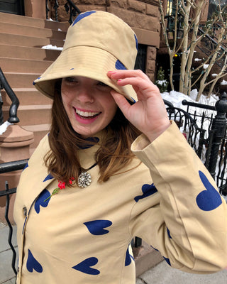 model wearing tan trench coat with blue heart print and matching hat