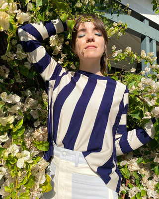 model wearing navy and white striped sweater with blue and white denim pants