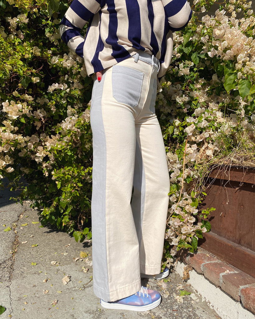 woman wearing navy and white striped sweater with white and blue color block jeans and iridescent sneakers