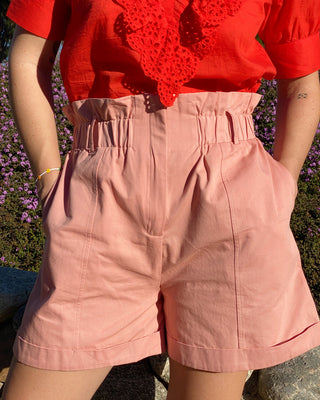model wearing pink shorts with red ruffle-front top