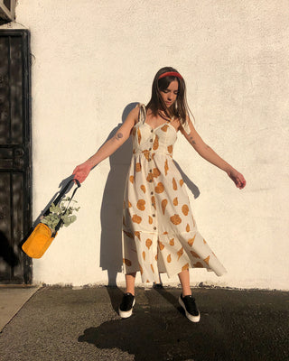 woman wearing white midi dress with leopard shell pattern and black platform sneakers, holding a yellow sport bag with eucalyptus branches
